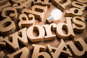 Words alphabets in scettered wood letters on the table with glowing light bulb as communication idea or words have power concept